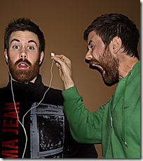 Man yelling into another's ear after removing their headphones--silly stuff (from Flickr)
